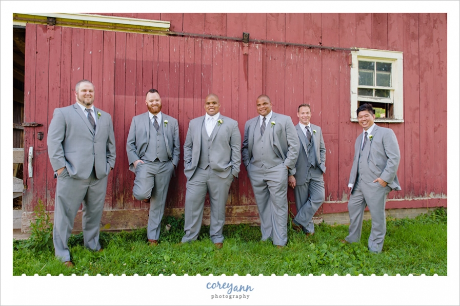 Groom and groomsman against red barn in Ohio