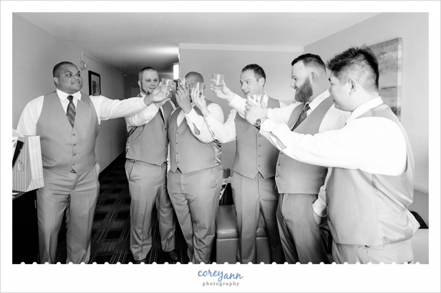 Groom and groomsman toasting before wedding